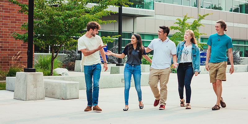 Students talking and walking across campus