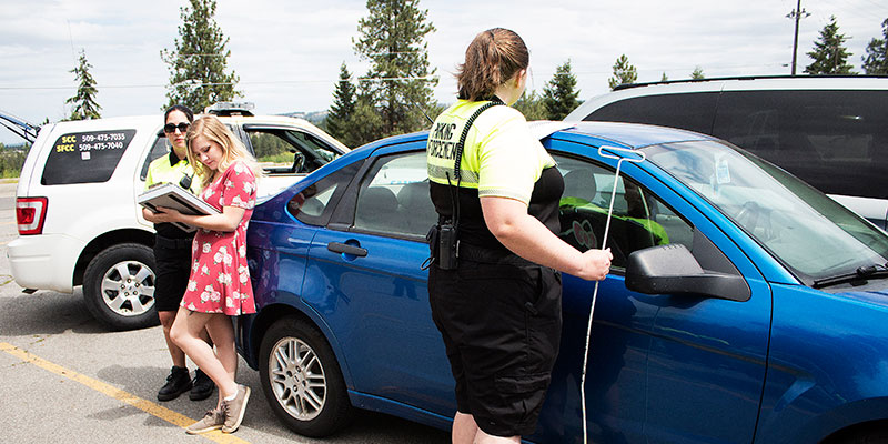 Campus Security assisting a student with unlocking her car.
