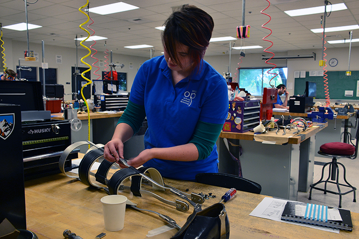 A student works on a brace, fitting metal side pieces into strips of leather.