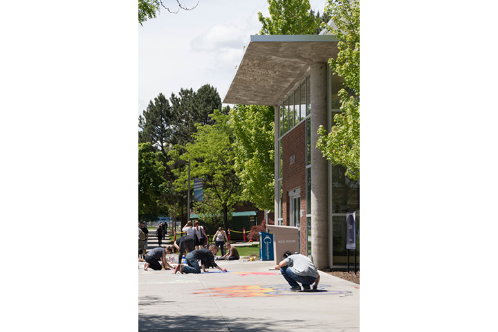 Students creating chalk drawings on sidewalk outside of the Library
