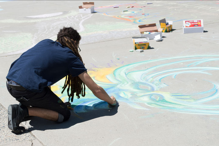Student creating chalk art in fron of the library