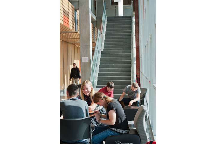 Five students seated together inside Music Building lobby