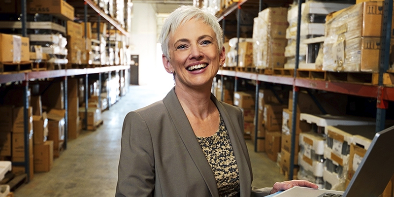 A mature woman in a business suit works at a laptop in a warehouse full of merchandise