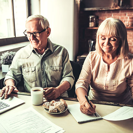 Older couple working at the table together.