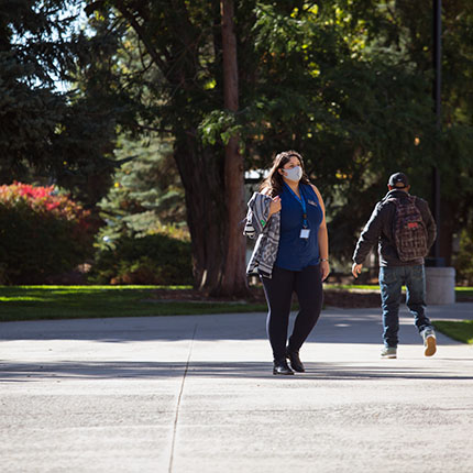 Student walking across campus with a mask on
