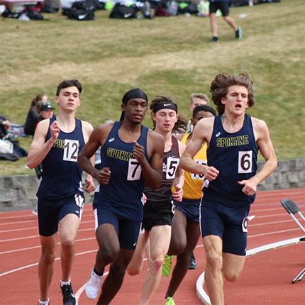 Students Travis Hicks 12, John Correa 7, and Anthony Carlascio 6 running during a track and field competition.