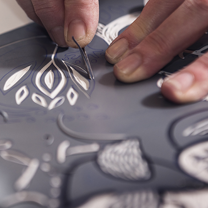 Hands carving a linoleum block for making a print