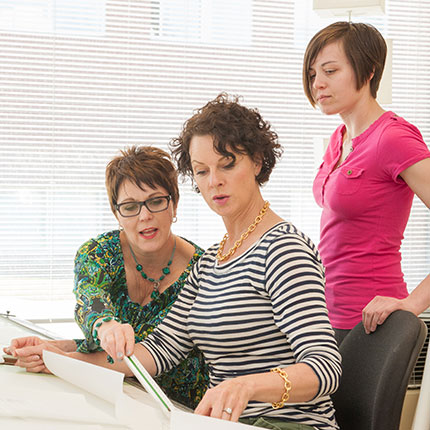Three women in interior design classroom