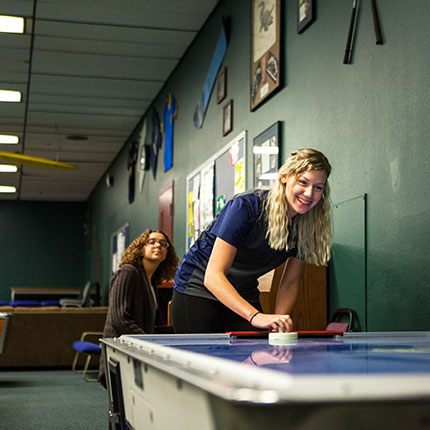 Girl playing air hockey in the recreation center.