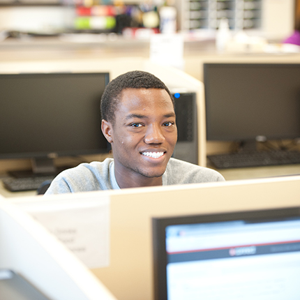 Young man sits at a computer