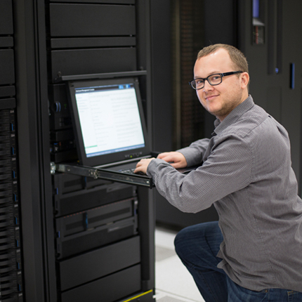 A programmer types at a laptop in a server lab