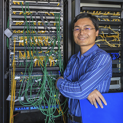 A man stands in front of a tower of servers
