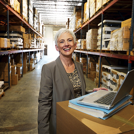 A smiling woman uses a laptop in a warehouse full of goods