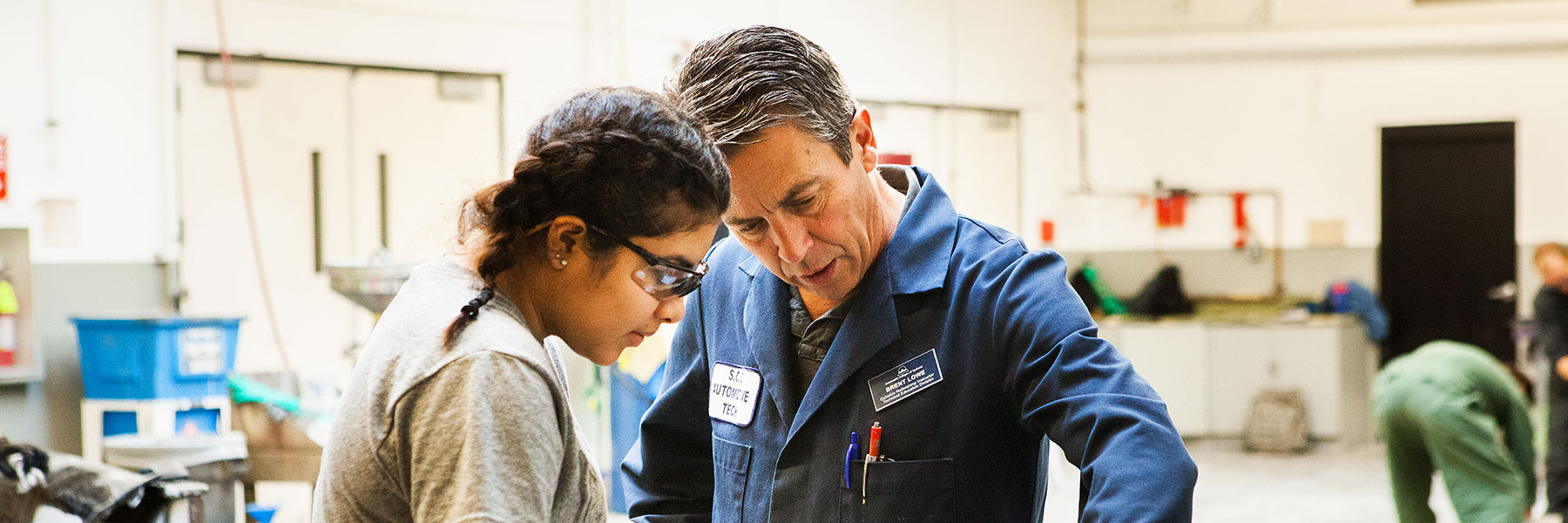 An automotive tech teacher helps a female student in the workshop