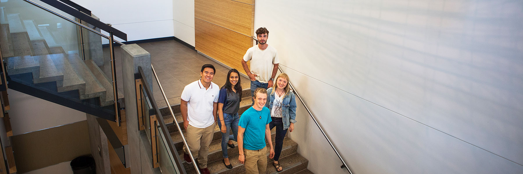 Students smiling on the stairs in the Gateway Building.