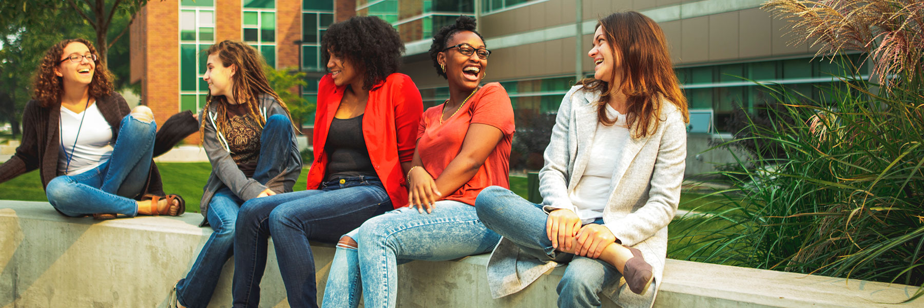 Five young women outside on campus laughing
