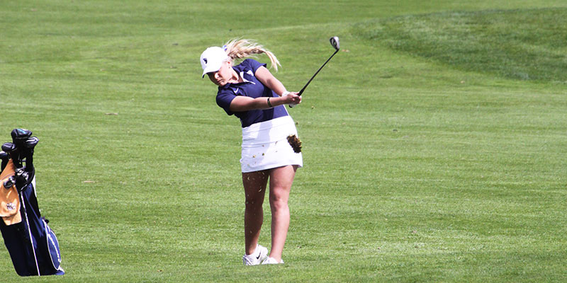 Women's golf player swinging the club