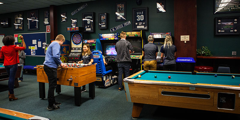 Students play foosball and pool in the Student Union Building rec room