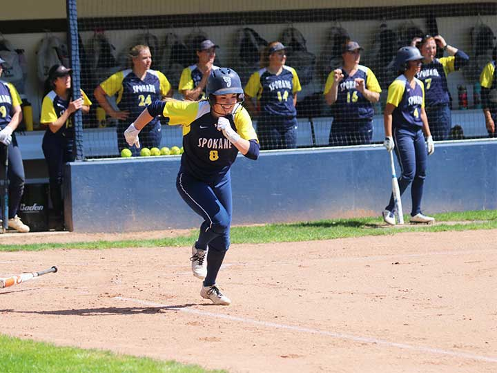 Softball player running to first base
