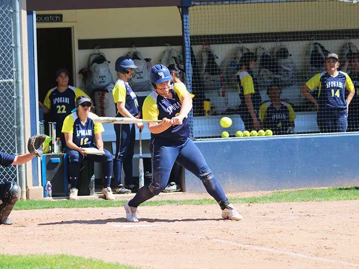 Softball player hitting the ball mid swing with team in view