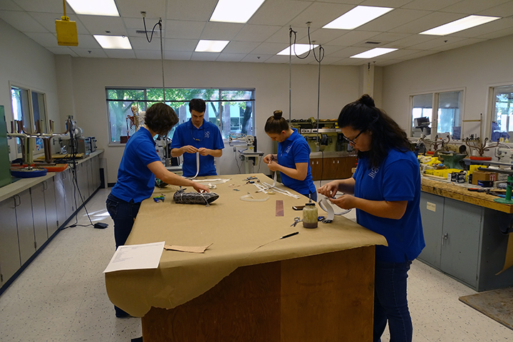 Students work on individual harnesses for various pieces of equipment