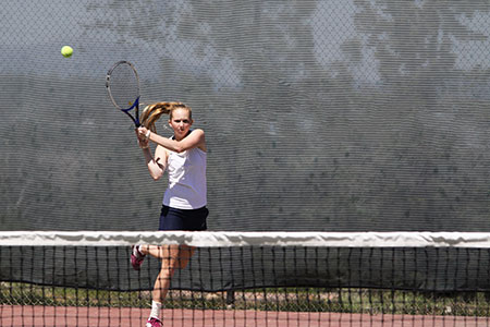 A female player swings her racket to hit a tennis ball