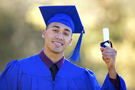 Graduate in cap and gown holding a diploma